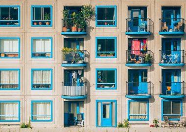 Façade d'immeuble beige avec petites fenêtres bleues et quelques balcons