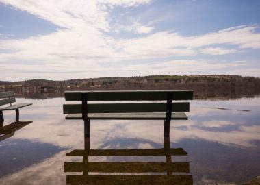 A bench is surrounded by water from a spring flood in Quebec on a sunny day