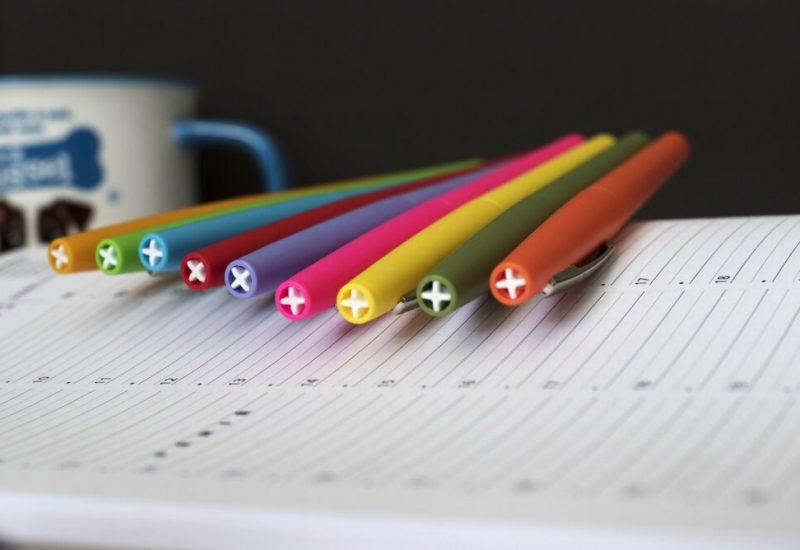 Un cahier avec des crayons de couleur et une tasse en arrière-plan