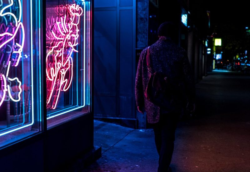 Person walking by dimly lit bar in Toronto Chinatown