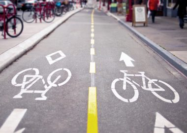 route gourdronnée avec un marquage au sol blanc et jaune indiquant une piste cyclable circulant dans les deux sens