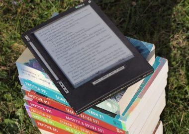 une tablette numérique poser sur des livres superposés.