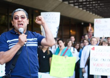 Byron Cruz speaks at a microphone in front of a row of protesters with signs