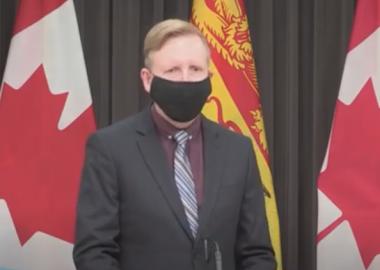 Dominic Cardy portant un masque noir devant un drapeau néo-brunswickois et canadien