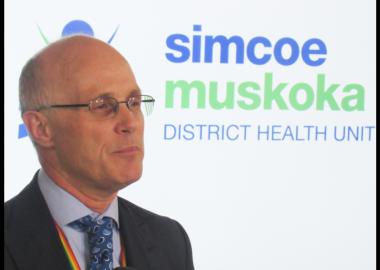 Le dr. Charles Gardner devant une pancarte du bureau de santé de Simcoe Muskoka
