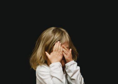 Une petite fille se couvrant les yeux sur un fond noir
