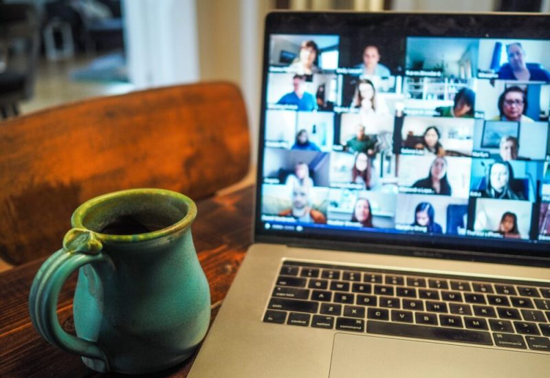 Video conference call on laptop screen. Blue mug placed beside laptop.