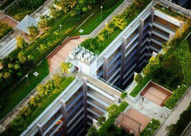 Un immeuble de plusieurs étages avec un toi vert. C'est une photographie en plongée