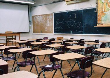Une salle de classe, cinq rangés de pupitres son devant un mur de tableaux noirs, un rideau à projection est baissé devant les pupitres.