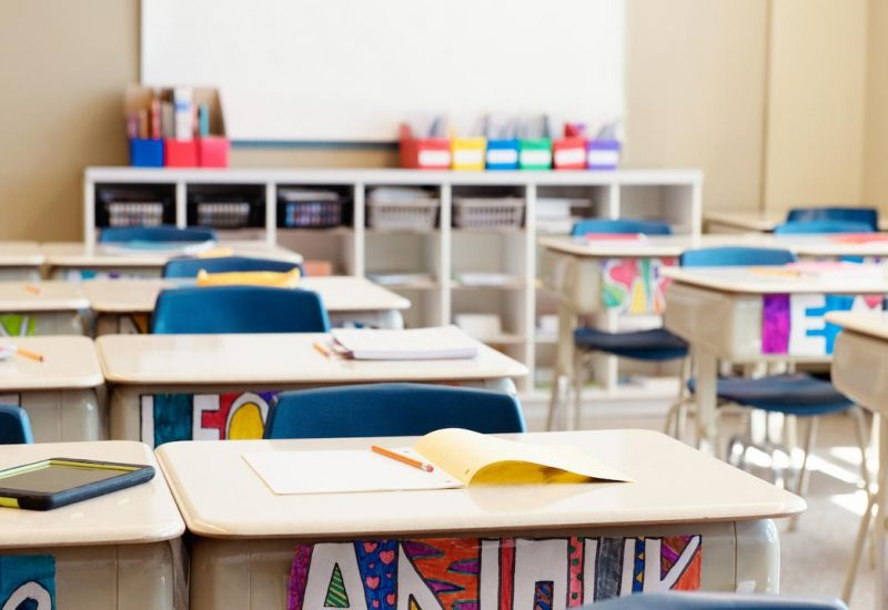 Une salle de classe lumineuse et colorée sans élèves avec des affaires sur les tables