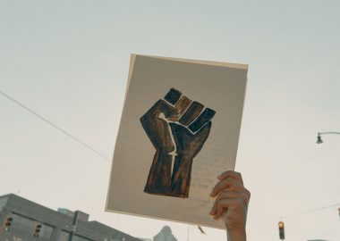 An image of a painting of a black fist representing Black Lives Matter. It is held up against a blue sky.