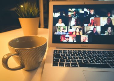 photo of zoom room on laptop screen with coffee mug placed beside it.