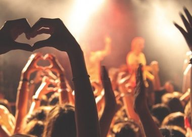 Une photo d'un concert, avec quelqu'un qui fait un signe du cœur avec ses mains.