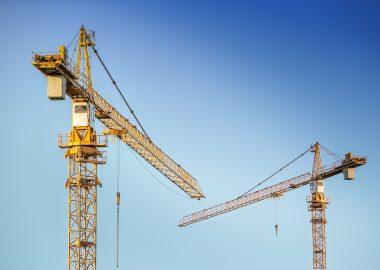 Deux grues de chantiers sur un ciel bleu. les grues sont jaunes