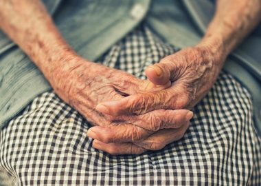 An elderly person folds their hands in their lap.