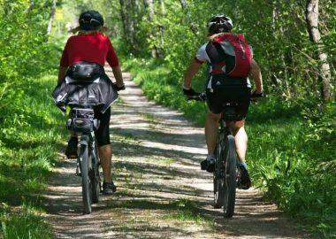 Deux personnes font du vélo sur une piste cyclable bordée de verdure