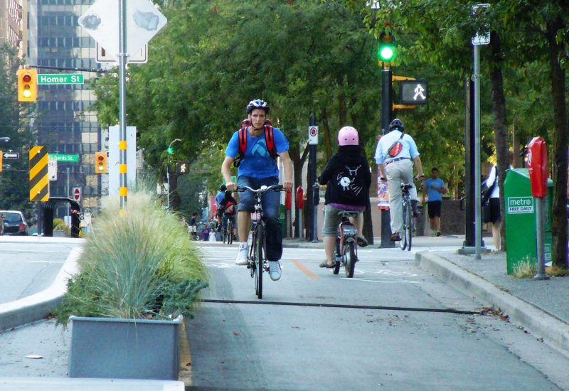 A daytime photo of bikers along Dunsmuir Bike Lane in downtown Vancouver