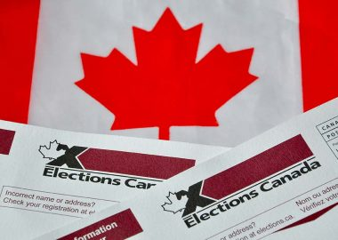A Canadian flag sits behind the top of two voting ballots for Elections Canada