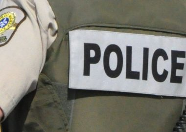 A photo of the word police (SQ) on the back of a police vest.