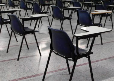 Empty desks are shown in a classroom.