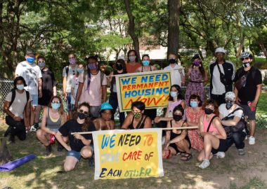 A photo of the Encampment Support Network (ESN) community holding signs.