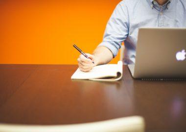 Un homme devant un ordinateur s'apprête à écrire. Il est assis sur une table en bois devant un fond orange.