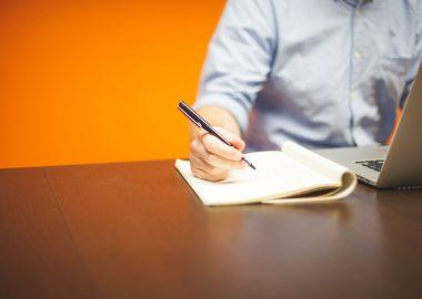 Un homme, entrepreneur est assis et écrit avec un stylo noir sur un block note.