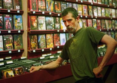 A man standing in front of shelves of movies