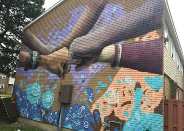 A painted mural of several multi-coloured fists joined in unity, painted on the side of a brick wall