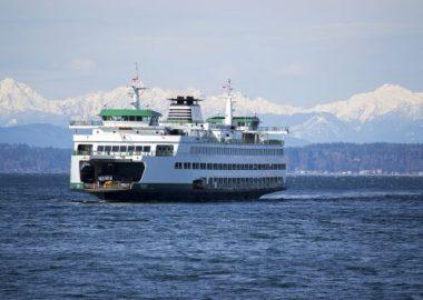 Un large bateau blanc vogue sur une étendue d'eau. On peut observer les montagnes de la Colombie-Britannique à l'arrière-plan.