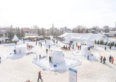 Le parc du voyageur en hiver, une vue élvée, des personnes circulent entre des sculptures de neige.
