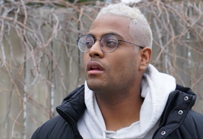 A headshot of Fitsum Arguy, with short white hair, a shite hoodie, a black jacket, and glasses, framed by naked trees in the background, and looking triumphantly towards the future.