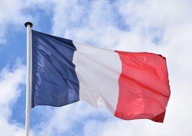 Le drapeau bleu blanc rouge de la France flotte dans le vent devant un ciel bleu et quelques nuages blancs.