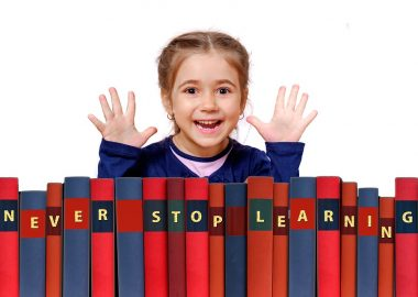 Une petite fille devant des livres