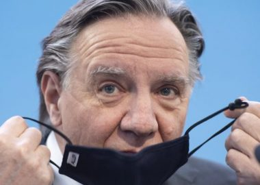 Picture of Premier Legault putting on a face mask.