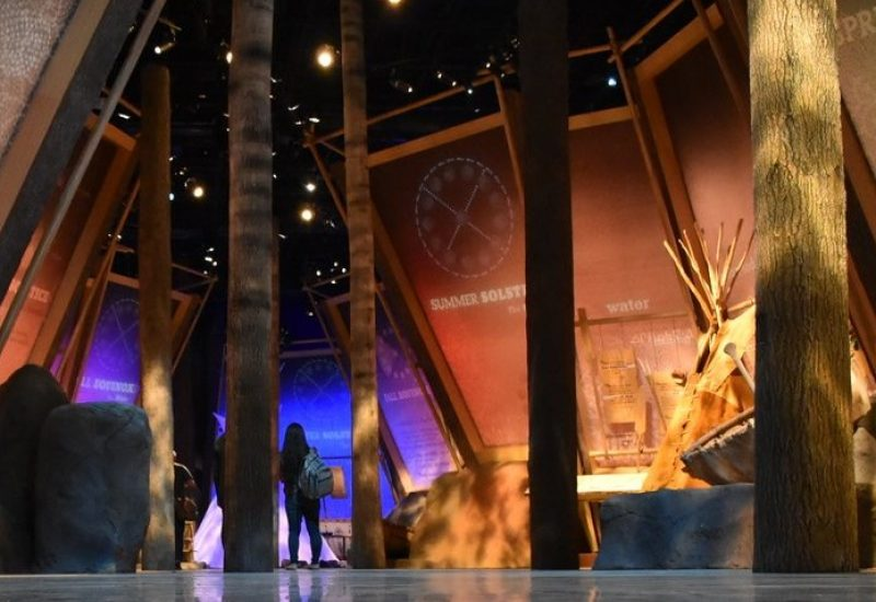 Indigenous lady looking at art display at Fort Edmonton Park exhibit