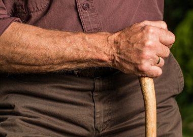 Bras d'une personne agée qui tient un canne.