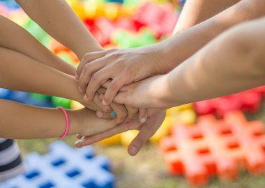 Des mains d'enfants devant des signes dièses de différentes couleurs