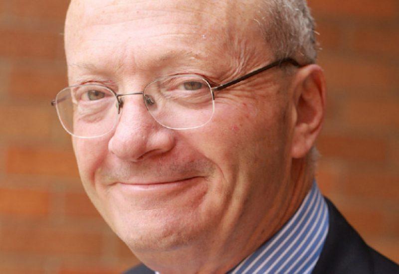 A close up headshot photo of a grinning Hugh Segal.