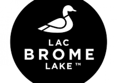 Black circle with a white duck picture and the words Lac Brome Lake