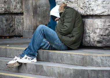 Un itinérant recroquevillé assis dans des marches en béton devant un édifice en pierres.