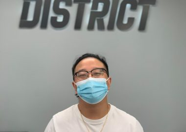 A man with a medical mask standing in front of a wall with a sign on it.