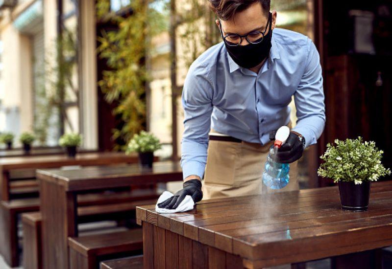 Un homme blanc avec un masque nettoie une table dans un café.