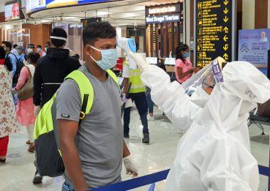 Un passager indien reçoit un test de la COVID-19 par une femme en équipement de protection individuelle avant de monter à bord.