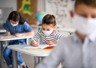 De jeunes élèves portent un masque en salle de classe et écrivent.