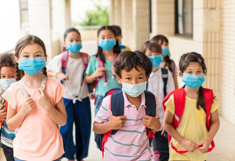Plusieurs enfants portant le masque s'apprêtent à retourner en salle de classe.