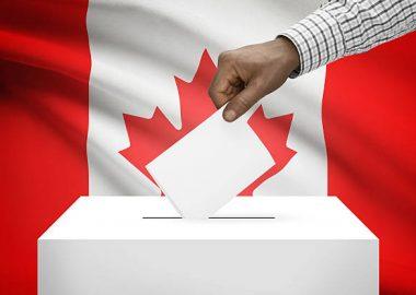 Le bras d'un homme noir, portant une chemise carreautée, dépose un carnet de vote dans une boite blanche, devant le drapeau canadien.