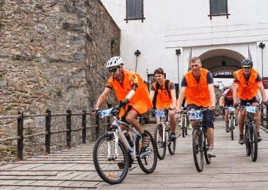 Des hommes au chandail orange qui font du vélo.