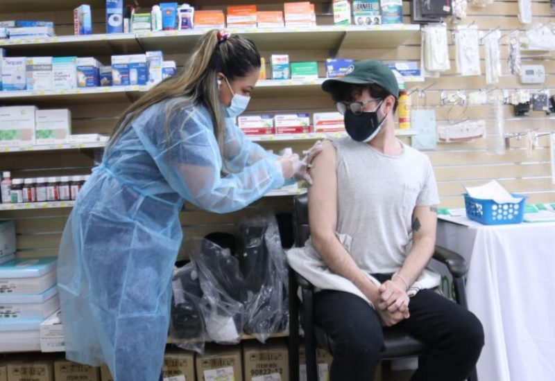 A person is sitting down while a person standing gives them a needle shot inside a clinic