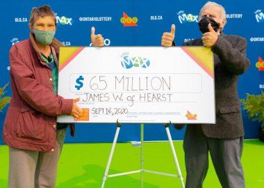 Le couple gagnant en train de tenir leur chèque de 65 millions avec un pouce en l'air